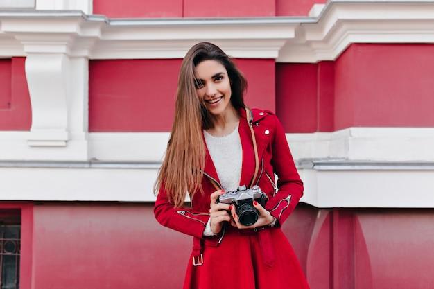 Signora carina con acconciatura lunga in piedi con la fotocamera sullo spazio di architettura