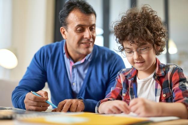 父親と一緒に机に座って、自宅で遠隔教育中に宿題をしている間、焦点を合わせているように見える眼鏡をかけているかわいいラテン系の少年。オンライン教育、ホームスクーリング、親子関係