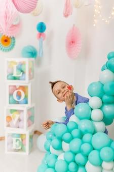 Симпатичный смеющийся мальчик с красным сердцем на щеке, выглядывающий из-за ярких воздушных шаров для вечеринок