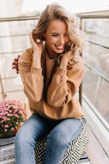발코니에서 포즈를 취하는 귀여운 웃는 소녀. 꽃 근처에 앉아 우아한 유럽 숙 녀의 초상화.