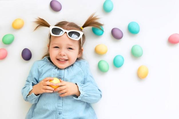 Cute laughing girl on a white easter background with colored eggs
