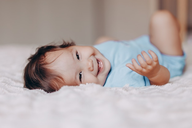 Cute laughing one year old girl lying on bed and looking at camera touch her feet