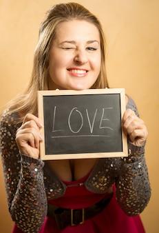 Симпатичная смеющаяся женщина позирует со словом «любовь», написанным на доске