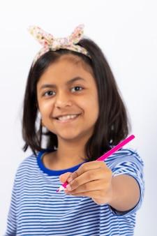 かわいい左利きの女の子がノートに鉛筆で書いています。