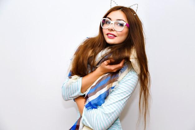 Ritratto di moda stile di vita carino di giovane donna graziosa castana con capelli lunghi incredibili, trucco fresco e luminoso, divertimento e gong pazzo, orario invernale, sciarpa calda accogliente, occhiali alla moda e accessori.