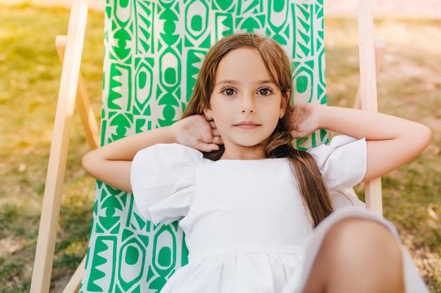 Carina ragazza leggermente abbronzata in abito bianco che riposa in chaise-longue verde trascorrere le vacanze in giardino. piccola signora dai capelli scuri sdraiata sulla sedia estiva con le mani sotto la testa.