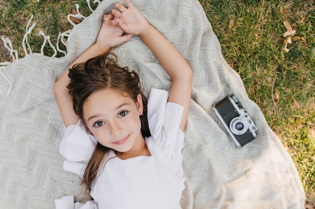 Cute lightly tanned girl with shiny beautiful eyes posing on blanket with camera during summer weekend. overhead portrait of brown-haired female kid lying on the grass and dreaming.