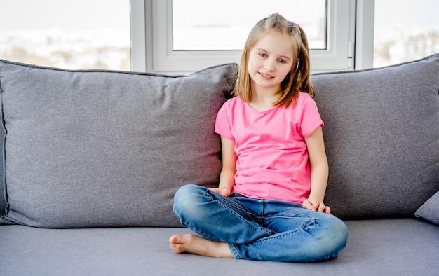 明るい部屋で灰色のソファーに座っているかわいいlitle女の子
