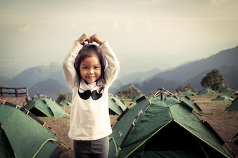 Cute litte asian girl having fun in the camp in vintage color filter