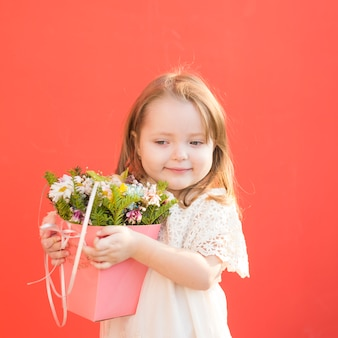 Cute litte bridesmaid holding flowers
