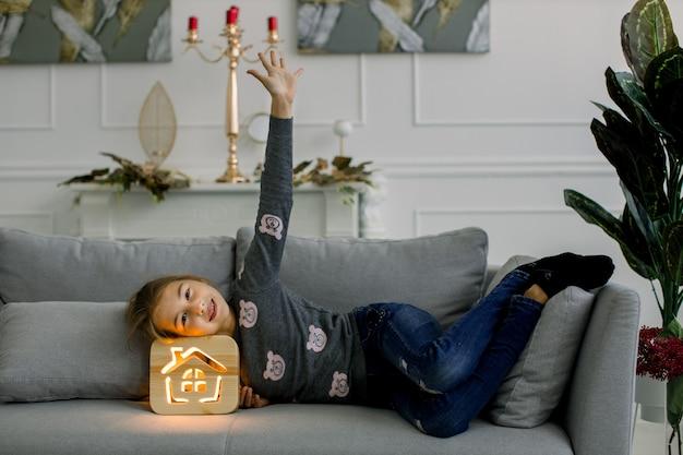 Милая маленькая 10-летняя девочка в повседневной одежде, лежа на сером диване у себя дома и опираясь головой на красивый стильный деревянный ночник. промо детские и ночники.