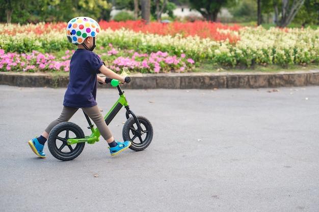 かわいい2〜3歳の幼児男の子の子供が安全ヘルメットを着用して日当たりの良い夏の日に最初のバランスバイクに乗ることを学び、公園でサイクリングの子供、コピースペースを持つ幼児のコンセプトで自然を探る