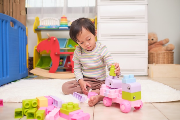Cute little 2 years old asian toddler girl child having fun playing with colorful plastic toy blocks on floor at home