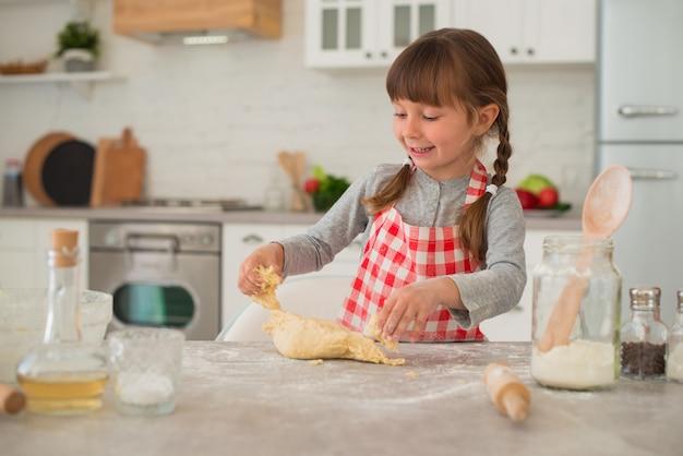 おさげ髪のかわいい4歳の女の子は、台所のテーブルに麺棒で生地を広げます。