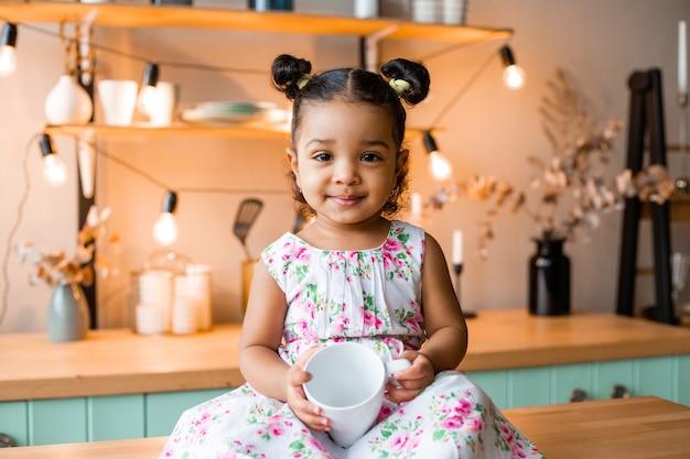 Милая маленькая афроамериканская девочка дома на кухне