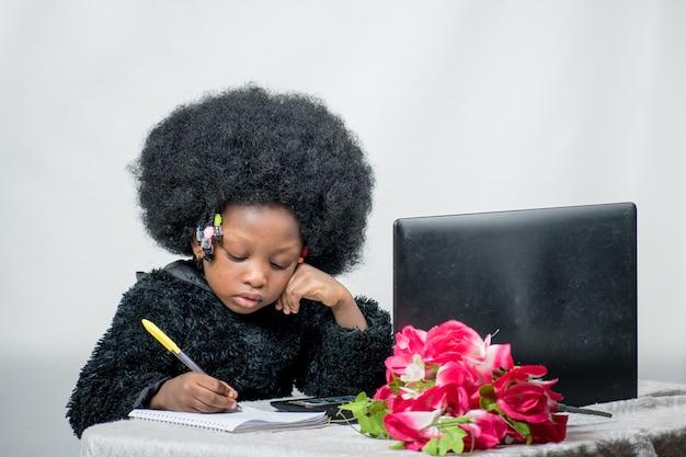Милая маленькая африканская девушка с афро-прической пишет ручкой и ноутбуком рядом с ней