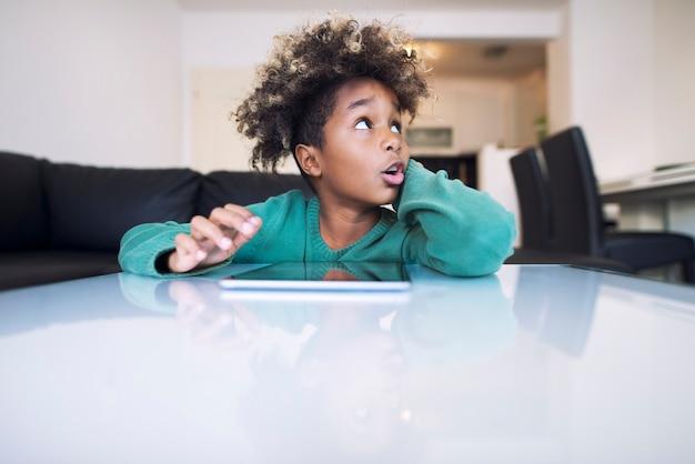 Симпатичная афро-девочка с забавным лицом смотрит в сторону и просматривает интернет на своем планшете