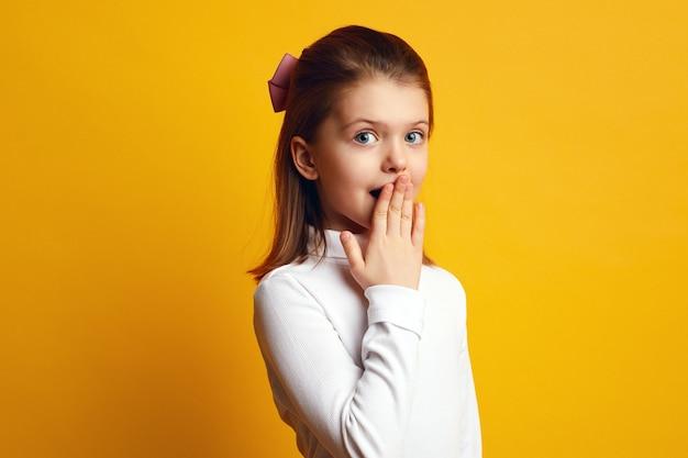 Милая маленькая удивленная девушка в повседневной одежде, прикрывая рот рукой