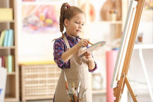 Милый маленький художник рисует картину в студии