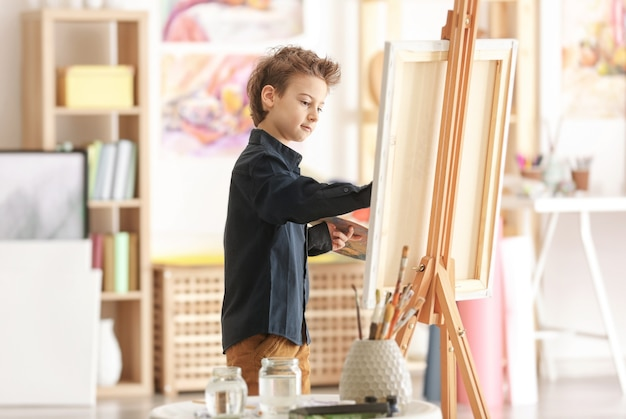 Cute little artist painting picture in studio