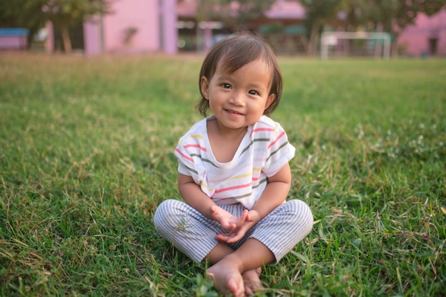 Cute little asian 1 - 2 years old toddler baby girl child smiling at camera, barefoot practices yoga & meditating outdoors
