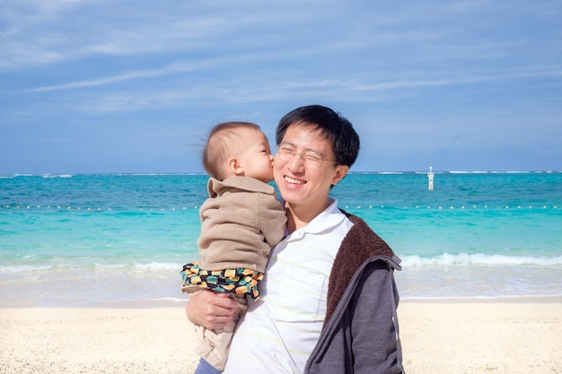 Cute little asian 1 year old / 18 months toddler baby boy child kiss dad on beautiful white sand beach