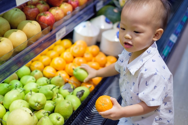 Cute little asian 18 months / 1 year old toddler baby boy child shopping in a supermarket