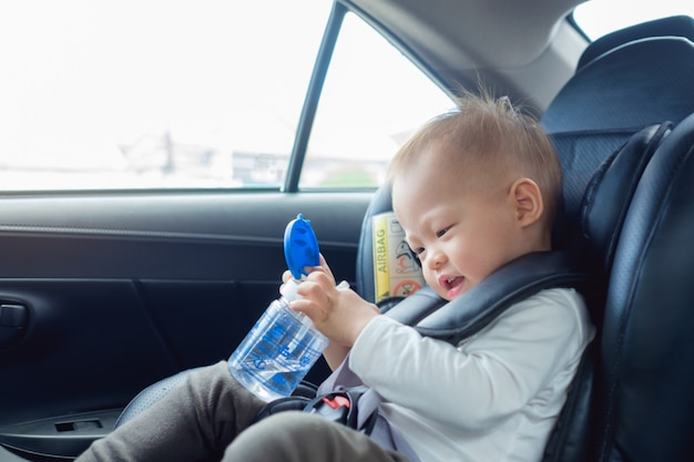 Cute little asian 18 months / 1 year old toddler baby boy child sitting in car seat holding and drinking water from cup