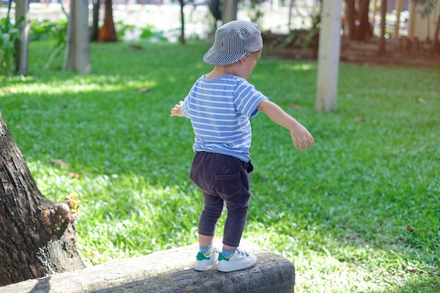 Cute little asian 18 months, 1 year old toddler baby boy child walking on balance beam in the park on nature in summer, physical, hand and eye coordination, sensory, motor skills development concept