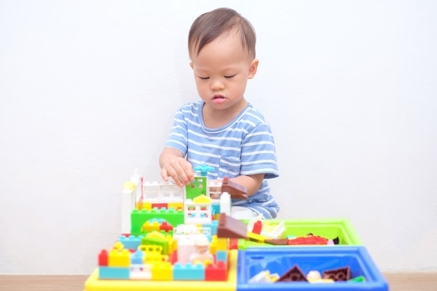 Cute little asian 18 months, 1 year old toddler boy child sitting on wooden floor having fun playing with colorful building blocks indoor at home, educational toys for young children concept
