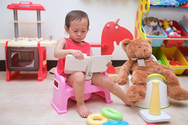 Cute little asian 18 months old toddler baby girl child sitting on potty and reading a book in play room at home with toys & teddy bear