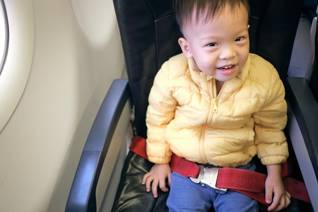 Cute little asian 2 - 3 years old toddler baby boy child smiling during flight on airplane