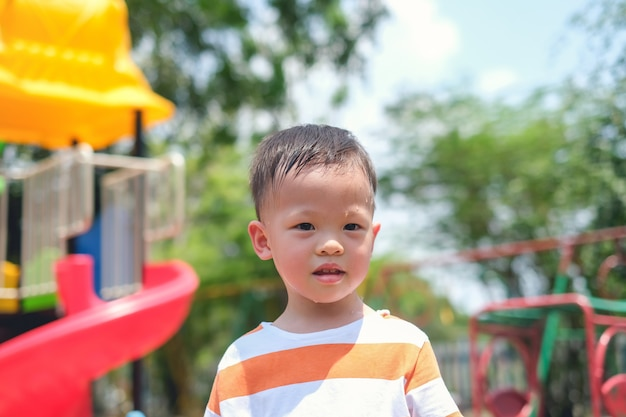 Cute little asian 2 - 3 years old toddler boy child sweating during having fun playing, exercising outdoor at playground, heat stroke concept