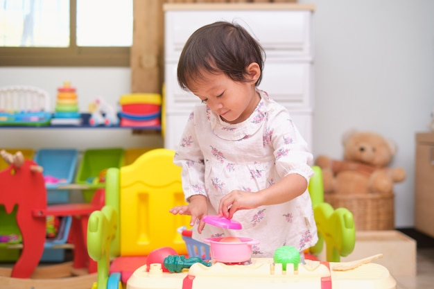 Cute little asian 2 - 3 years old toddler girl child having fun playing alone with cooking toys, kitchen set at home