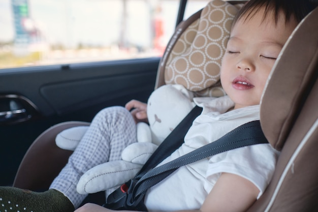 Cute little asian 2 - 3 years toddler baby boy child sleeping in modern car seat. child traveling safety on the road