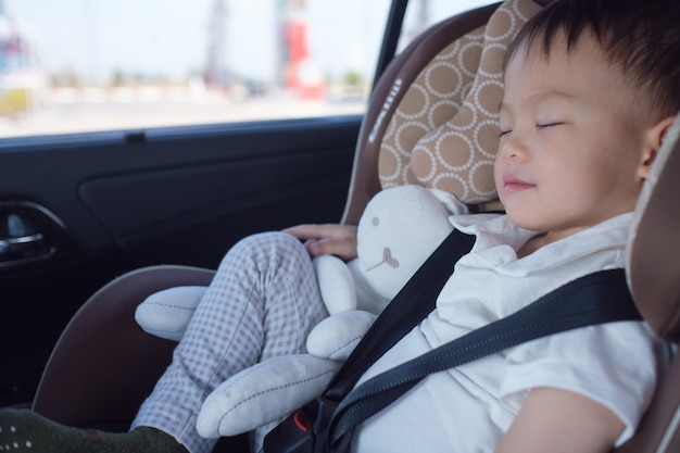 Cute little asian 2 - 3 years toddler baby boy child sleeping in modern car seat