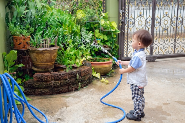 Cute little asian 2 year old toddler baby boy child having fun watering the plants from hose