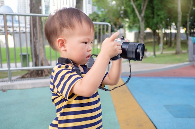Cute little asian 2 year old toddler boy wear camera strap taking photo using digital camera, looking at camera in park, kid photographing nature, explore & appreciate nature with toddlers concept