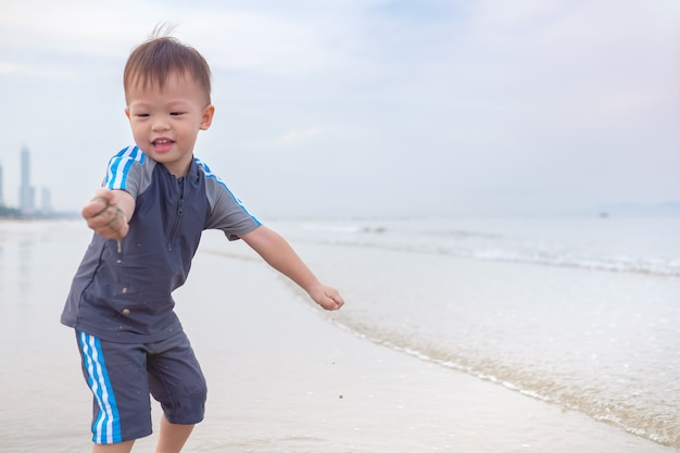 Cute little asian 2 years old toddler baby boy child on beach with dirty hands covered with wet sand. family travel, water outdoor activity on summer beach vacation, sensory play with sand concept
