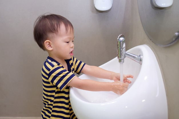 Cute little asian 2 years old toddler baby boy child washing hands by himself on white sink and water drop from faucet in public toilet / bathroom for kids, sanitation / hygiene concept
