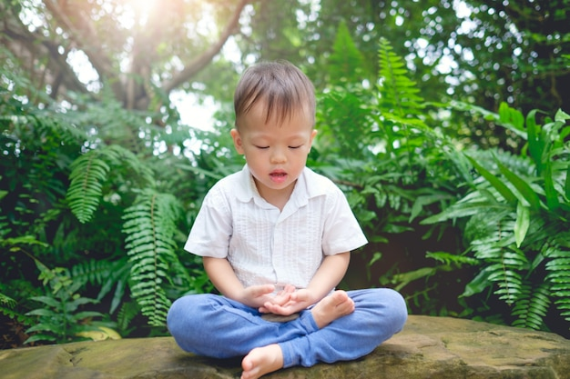 Cute little asian 2 years old toddler baby boy child with eyes closed, barefoot practices yoga & meditating outdoors on nature in springtime, beginner meditation, healthy lifestyle concept