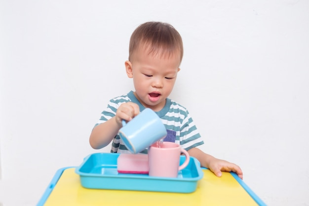 Cute little asian 2 years old toddler boy child having fun pouring water into cup, wet pouring montessori preschool practical life activities, fine motor skills, kid sense child development concept