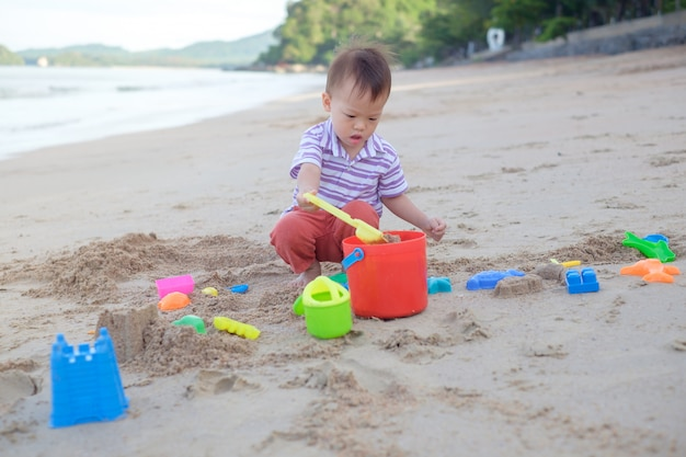 Cute little asian 2 years old toddler boy sitting & playing children's beach toys on beautiful sandy tropical beach