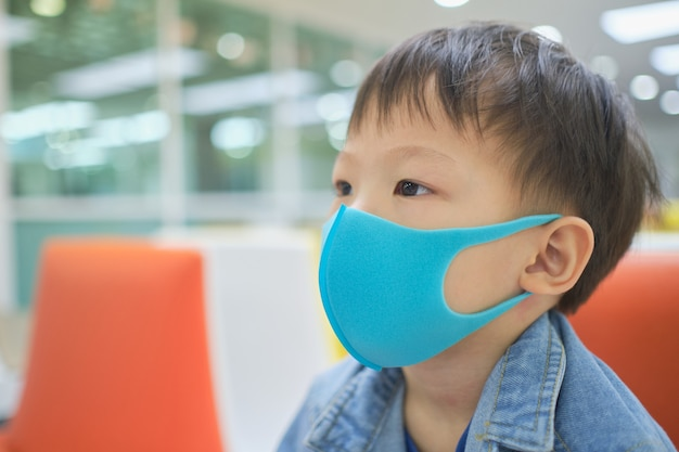 Cute little asian 3 - 4 years old toddler boy child wearing protective medical mask against pm 2.5 air pollution, kid sitting on sofa waiting to see doctor