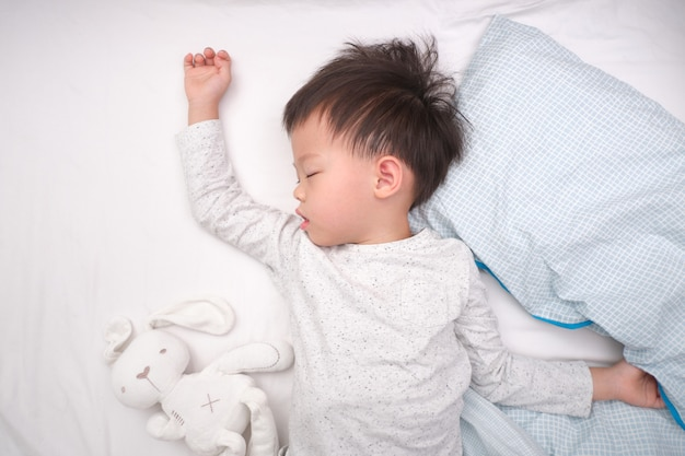 Cute little asian 3 - 4 years old toddler boy kid in pajama sleeping / taking a nap in bed , bedtime for kids concept