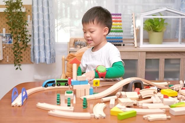 Милый маленький азиатский 5-летний мальчик весело играет с деревянным поездом