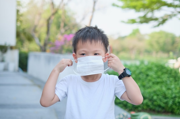 Cute little asian 5 years old toddler boy child wearing protective medical face mask by himself on nature at the park, concept of coronavirus, new normal lifestyle and air pollution pm 2.5 concept