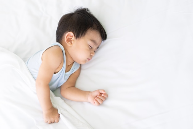 A cute little asian baby boy is peaceful sleeping on the bed in the bedroom with happiness moment