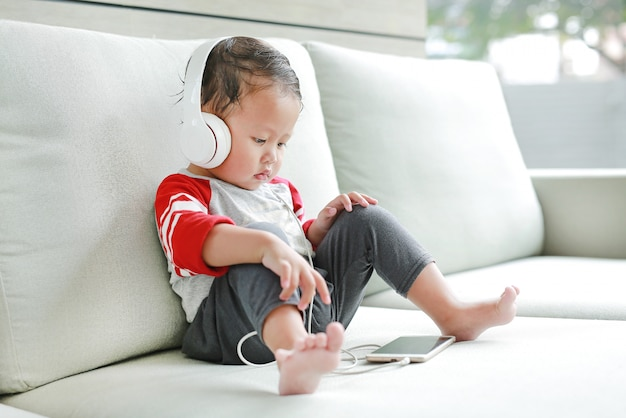 Cute little asian baby boy sitting on sofa and listening music at headphones while looking at phone.