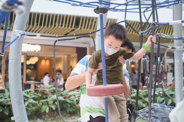 Cute little asian boy child wearing washable face mask climb on jungle gym at pulbic indoor playground with his father during covid-19 outbreak, new normal lifestyle concept - selective focus
